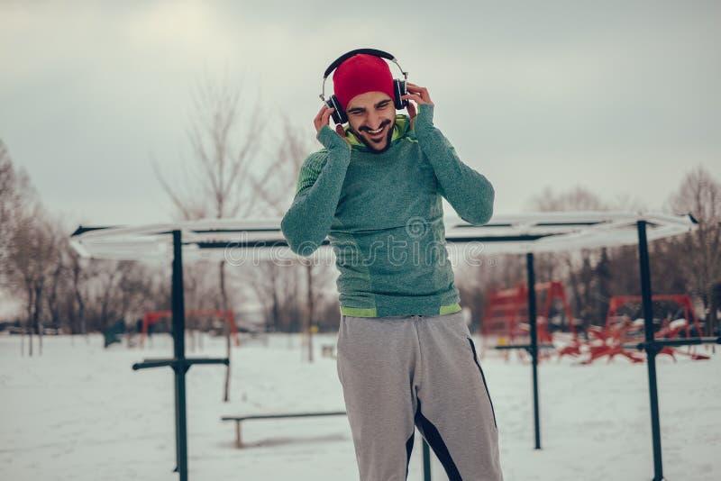 运动在他的锻炼的人听的音乐在冬日 图库摄影