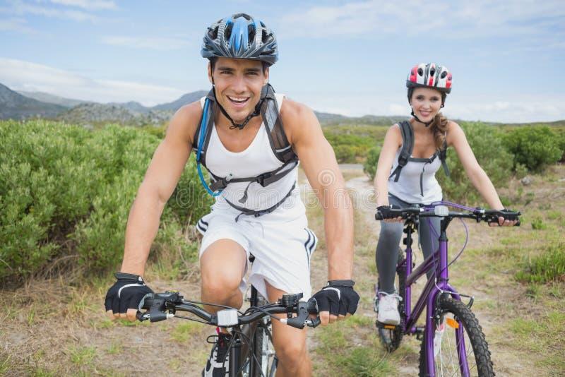 运动夫妇山骑自行车 图库摄影