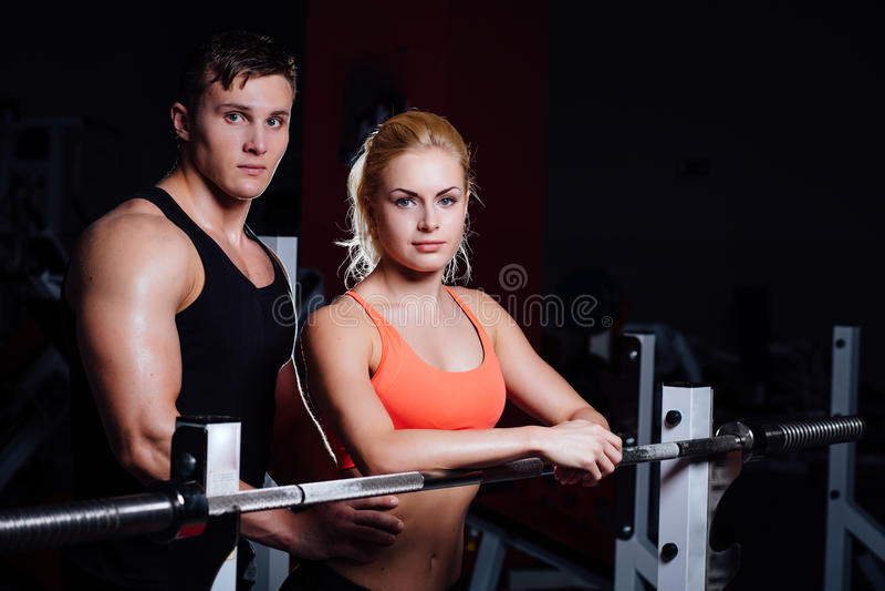运动夫妇-男人和妇女休息在锻炼之间在健身房的杠铃附近 库存照片