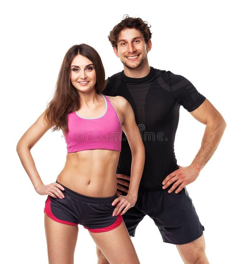 运动夫妇-男人和妇女在健身以后在白色行使 库存图片