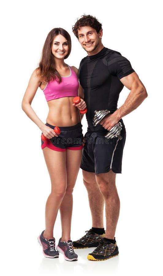 运动夫妇-男人和妇女有哑铃的在白色 免版税库存照片