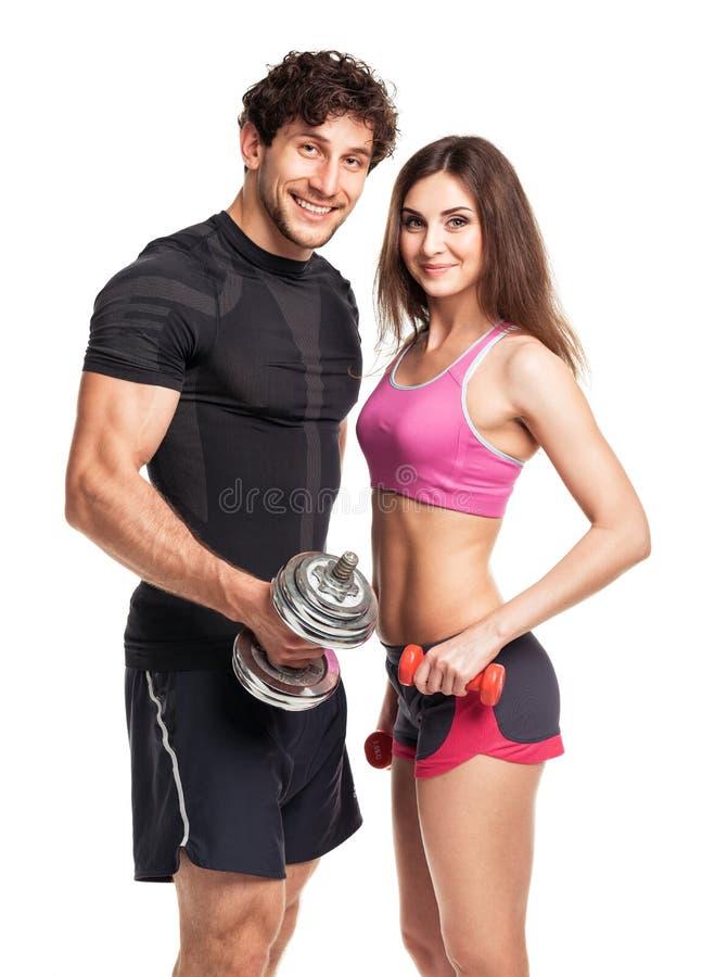 运动夫妇-男人和妇女有哑铃的在白色 免版税库存图片
