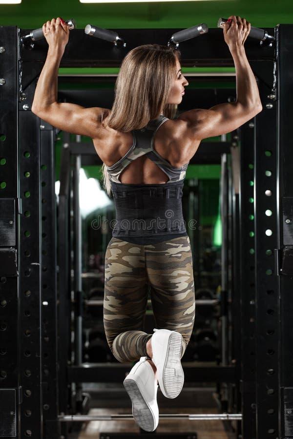 运动女孩做拔在单杠的锻炼 健身在健身房的妇女锻炼 免版税库存照片