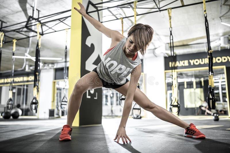 运动女孩做舒展在健身房 免版税库存图片