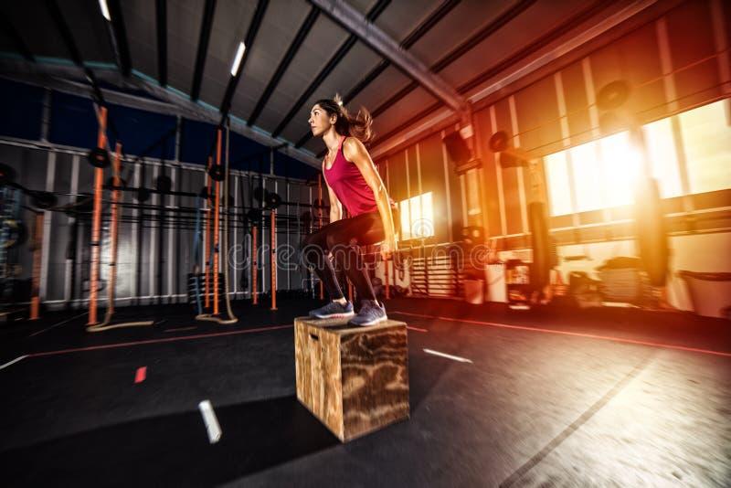 运动女孩把跃迁锻炼装箱在健身房 库存照片