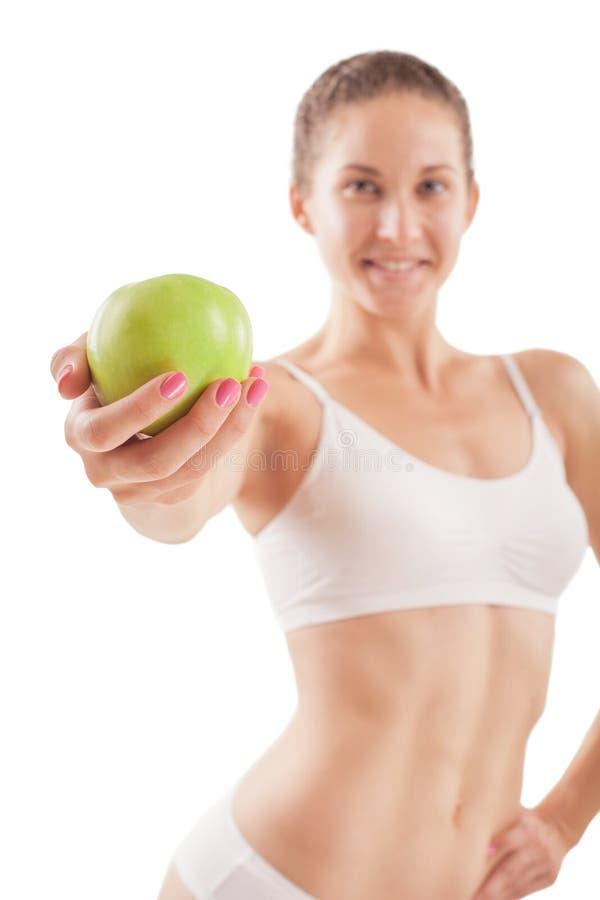 运动女孩用绿色苹果 免版税库存图片