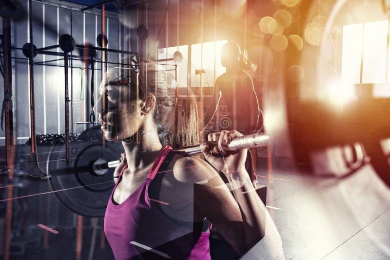运动女孩解决在与杠铃的健身房 女性,健康 r 免版税库存图片