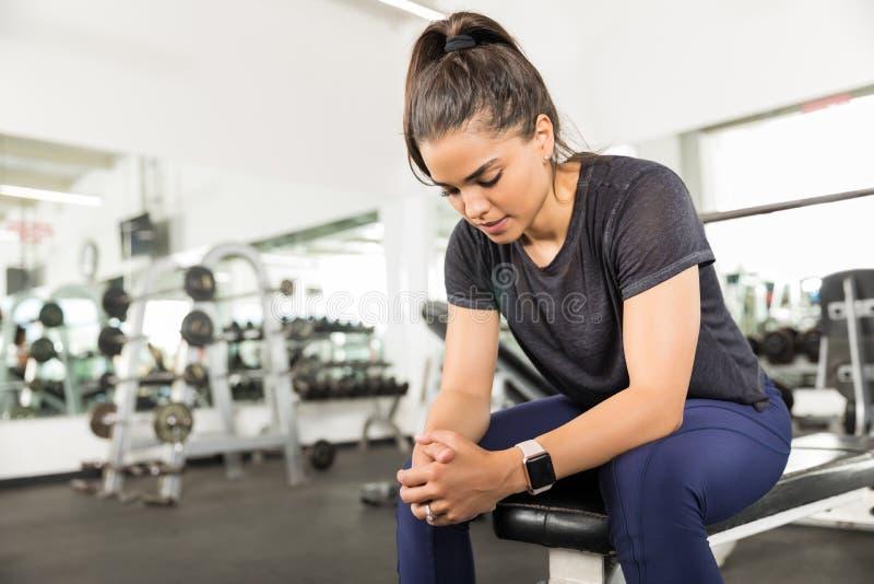 运动妇女坐长凳在健身俱乐部的锻炼以后 库存照片