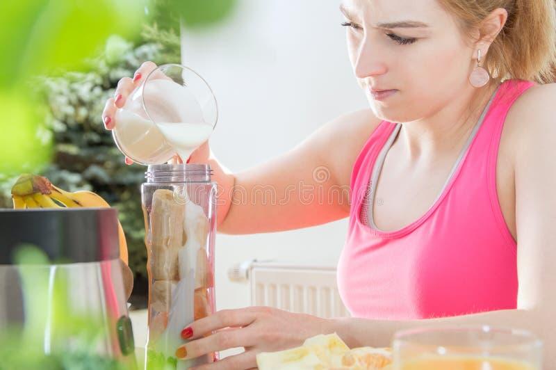 运动妇女拿着在桌上的酸奶 库存照片