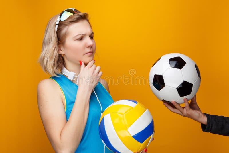 运动妇女选择在排球和足球之间在演播室 图库摄影