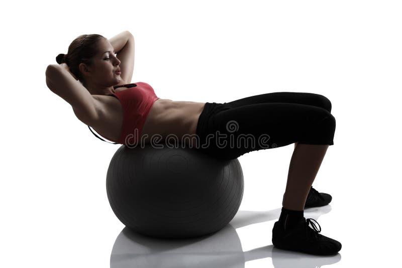 运动妇女震动有健身球的,体育画象新闻 免版税库存照片