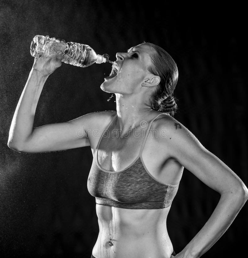 运动妇女饮用水的黑白照片 库存照片