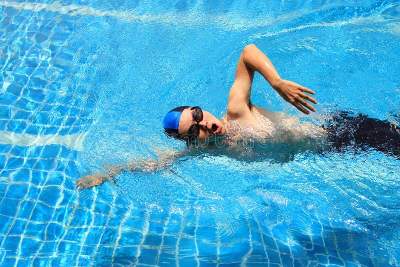 运动年轻人自由式游泳画象在水池、体育和健康生活方式概念的 库存照片