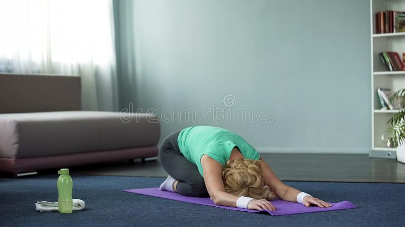 运动成熟女子实践的瑜伽摆在家、健身和健康,舒展 免版税库存照片