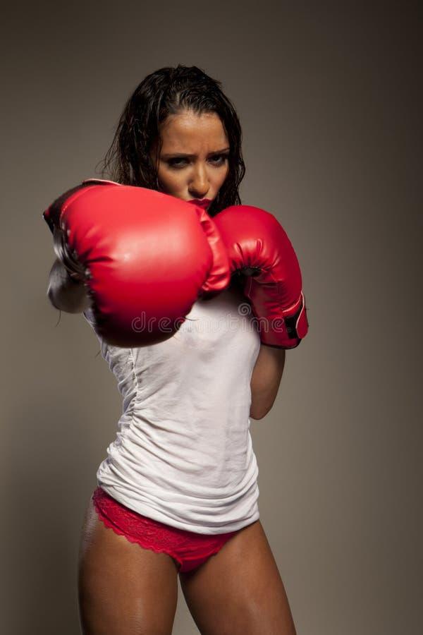 运动拳击手打孔机投掷的妇女 免版税库存图片