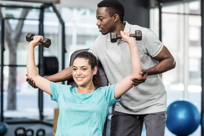 运动教练员帮助的妇女举的重量 免版税库存照片