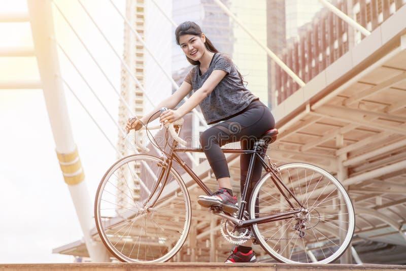 运动服乘驾的亚裔年轻体育妇女一辆自行车在城市 早晨 免版税库存照片