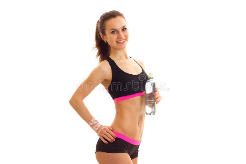 运动服微笑的年轻美丽的女孩保留在边和中间人水瓶的一只手 库存照片