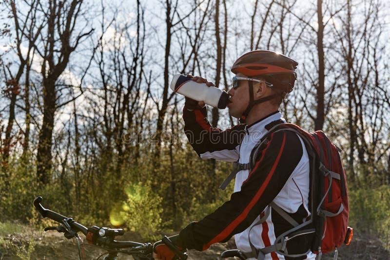 运动服的一个骑自行车者是从瓶的饮用水 免版税库存照片