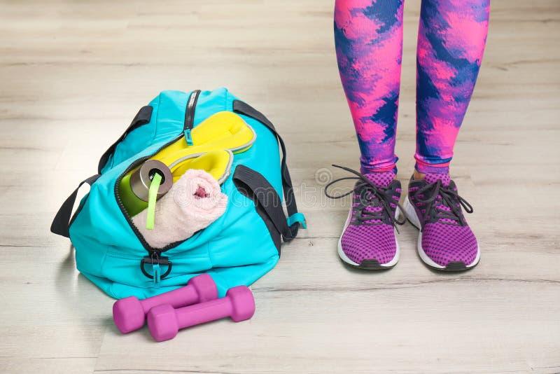 运动服的与户内健身房的少妇和袋子 免版税库存图片