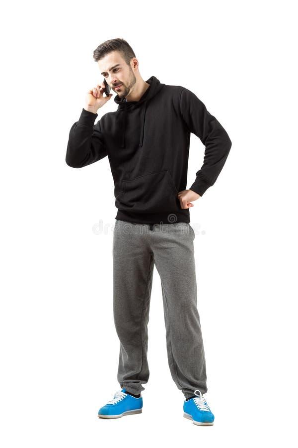 运动服的严肃的年轻人谈话在手机 免版税库存照片