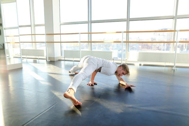 运动服的体操运动员训练在体育健身房的芭蕾纬向条花附近的 图库摄影