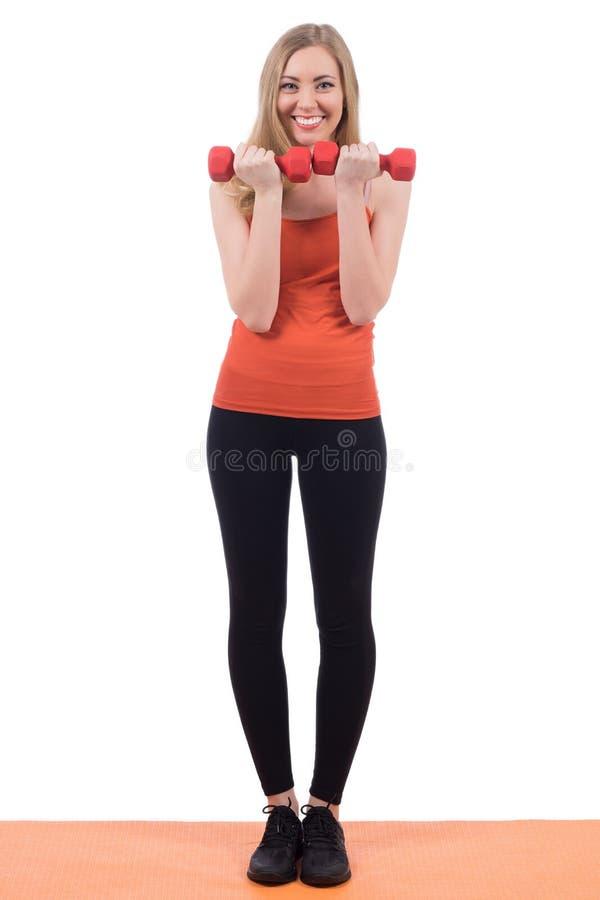 运动服的俏丽的妇女行使有哑铃的手 库存图片
