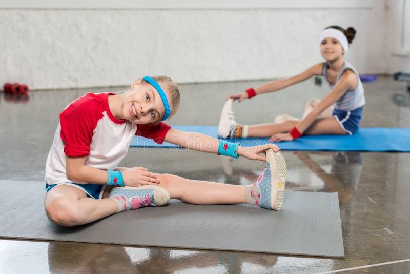 运动服的可爱的小女孩行使在健身房的瑜伽席子的 免版税库存照片