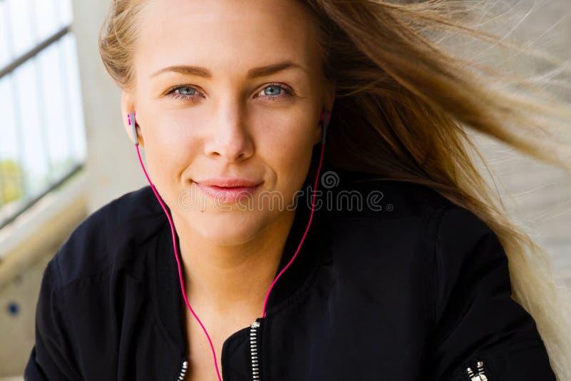 运动服的听到音乐的白肤金发的妇女接近的画象  库存照片