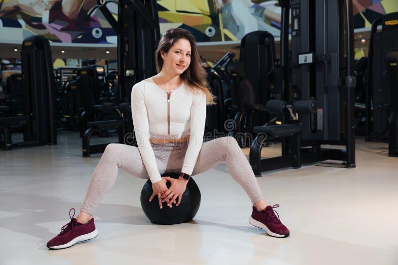 运动服的女孩在健身房训练 免版税库存照片