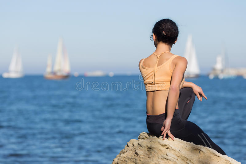 运动服的女孩观察乘快艇的赛船会 库存图片