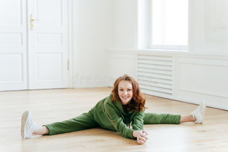 运动服的女性体操运动员,在瑜伽屋子里做腿分裂,坐地板,姿势,有锻炼锻炼,舒展腿, 免版税库存图片
