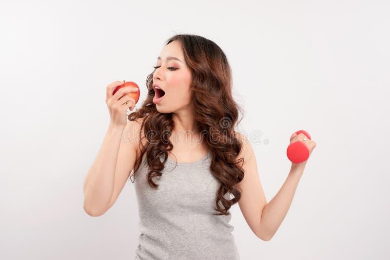运动服的年轻健身模型女子运动员有红色哑铃和绿色苹果的 免版税图库摄影