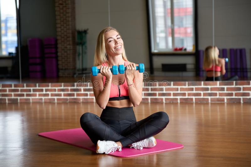 运动服的快乐的微笑的女孩在木地板上的健身房执行锻炼坐席子 免版税图库摄影
