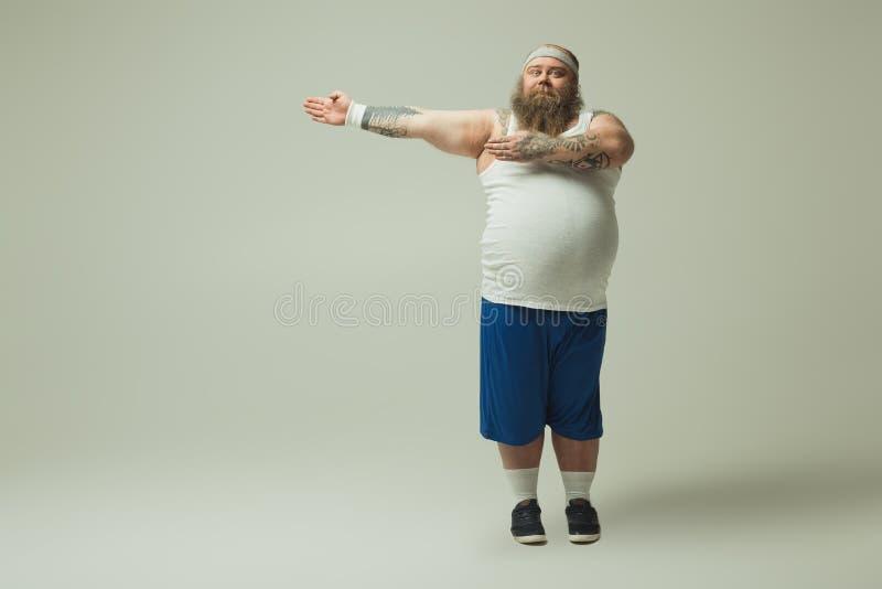 运动服的快乐的男性胖子指向手的斜向一边 免版税库存照片