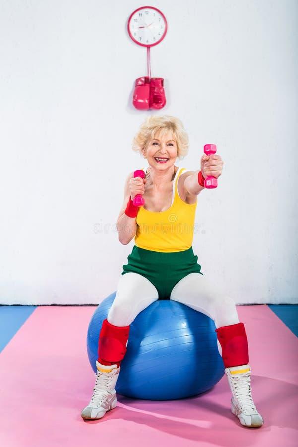 运动服的愉快的资深妇女坐健身球和行使 免版税库存照片