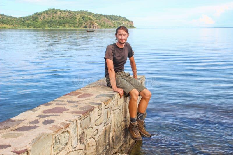 运动服的白白种人男性旅客坐在最长的湖的一个石码头在世界上 免版税库存图片
