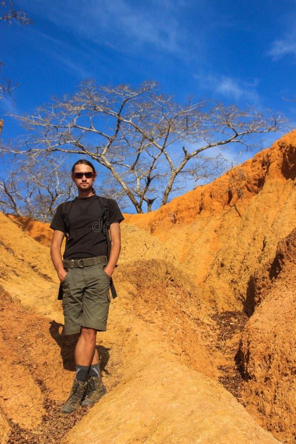 运动服的白白种人男性旅客:起动,短裤,反对明亮的黄色岩石的戴着眼镜立场在肯尼亚 免版税库存图片