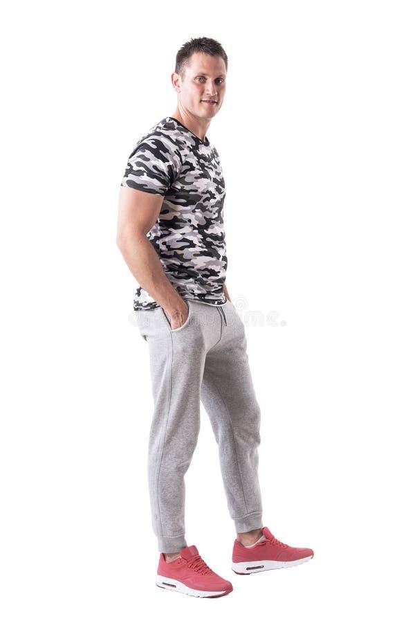 运动服的确信的愉快的英俊的年轻成人人用在口袋的手 免版税库存照片