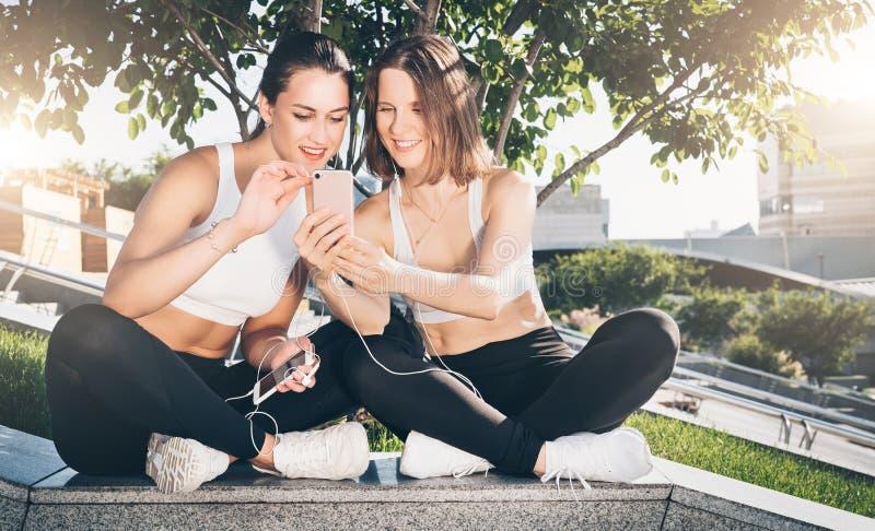 运动服的训练两位少妇的运动员在公园坐,在体育以后放松,使用智能手机 图库摄影