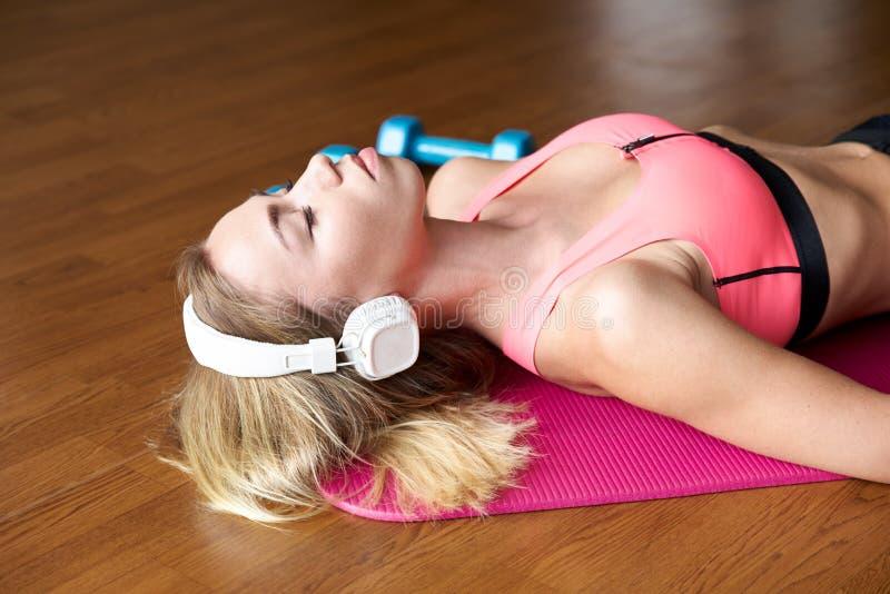 运动服的轻松和平安的女孩妇女闭上她的在体育席子的眼睛并且听到在白色耳机的音乐 免版税图库摄影