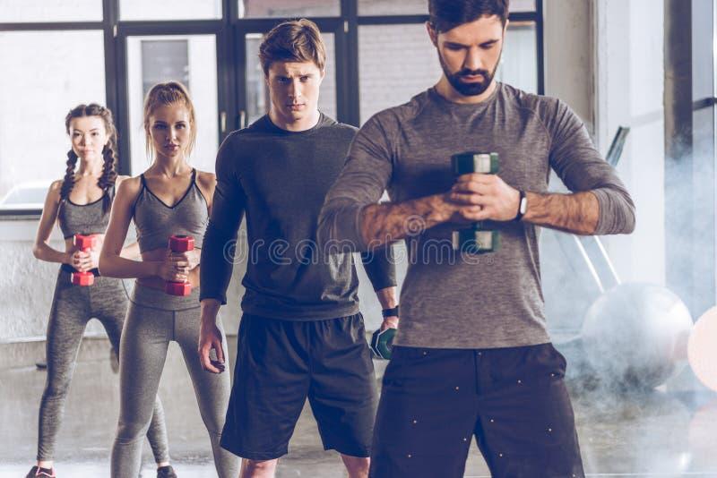 运动服的运动青年人有哑铃的行使在健身房的 图库摄影