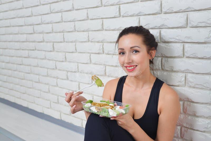 运动服的适合的健康妇女吃新鲜的沙拉的在健身锻炼以后 图库摄影