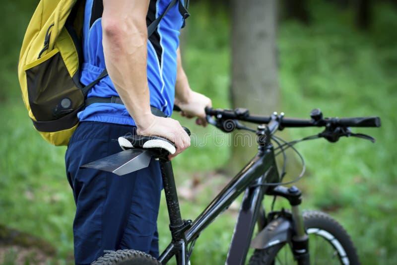 运动服的骑自行车者有反对绿色s背景的自行车的  免版税图库摄影