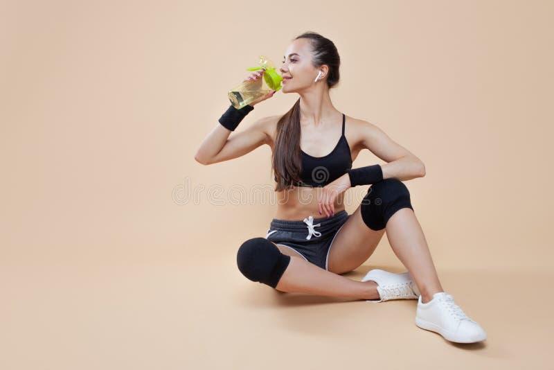 运动深色的女孩,体育制服的,在一种锻炼以后在她的手上坐,休息,与一个瓶,饮用水 免版税库存照片