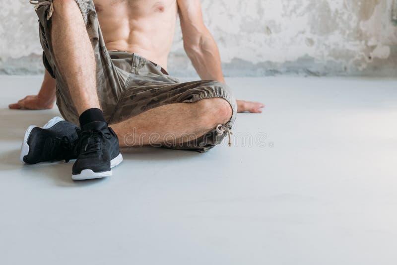 运动生活方式人坐胸部赤裸健身房的地板 免版税库存图片