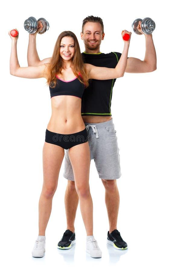 运动男人和妇女有哑铃的在白色 免版税库存图片
