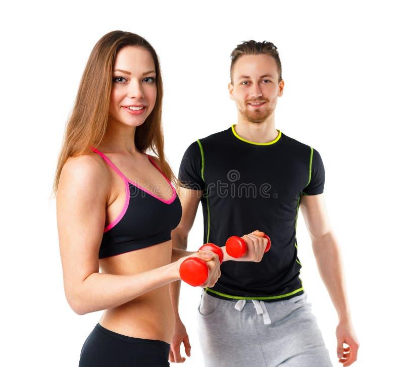 运动男人和妇女有哑铃的在白色 库存图片