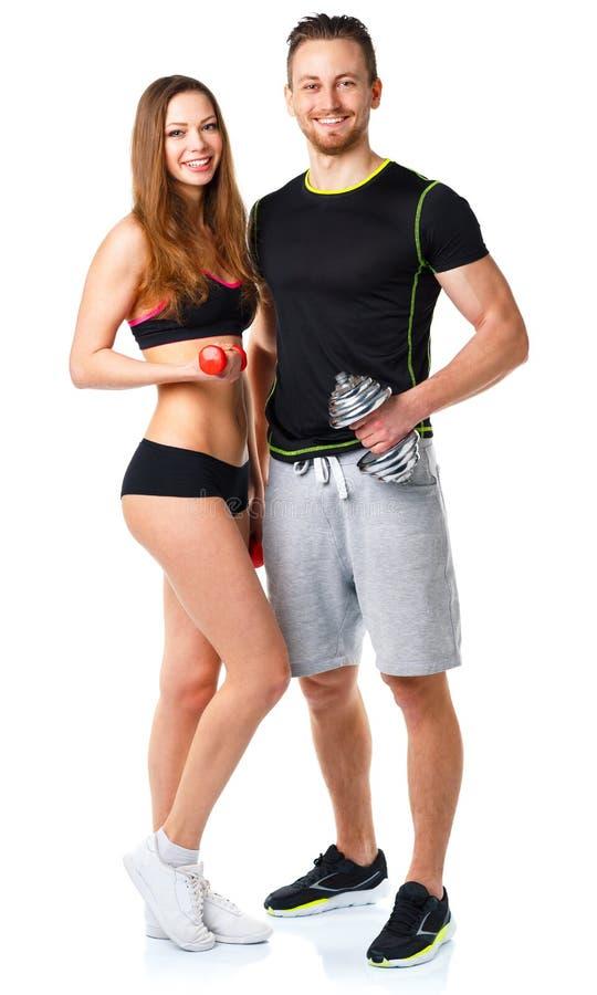 运动男人和妇女有哑铃的在白色 免版税库存照片