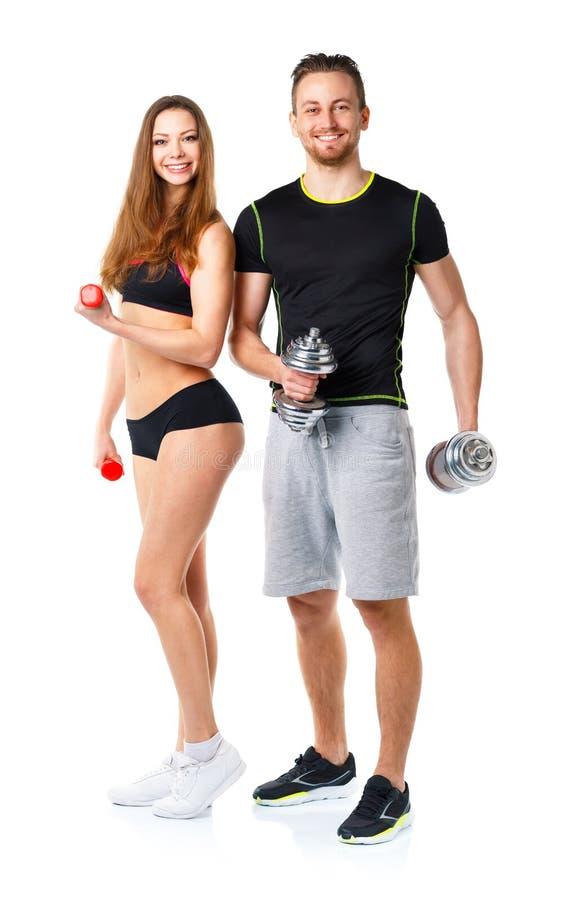 运动男人和妇女有哑铃的在白色 免版税图库摄影